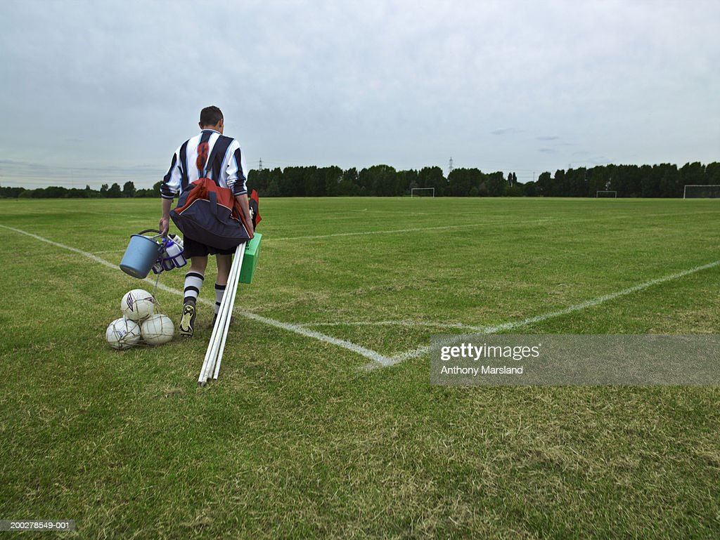 Football player carrying equipment onto pitch, rear view : Stock Photo