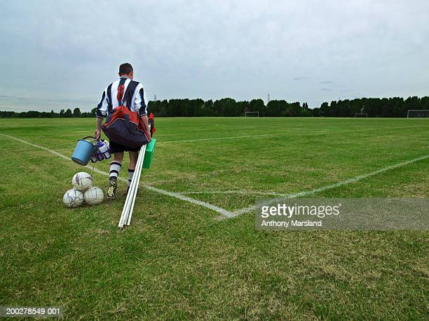 Football player carrying equipment onto pitch, rear view