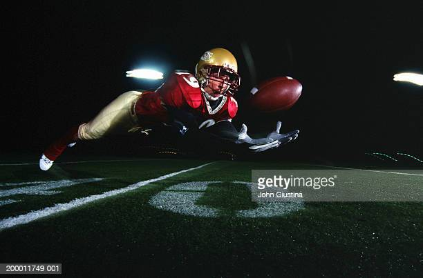 Football player diving to catch ball
