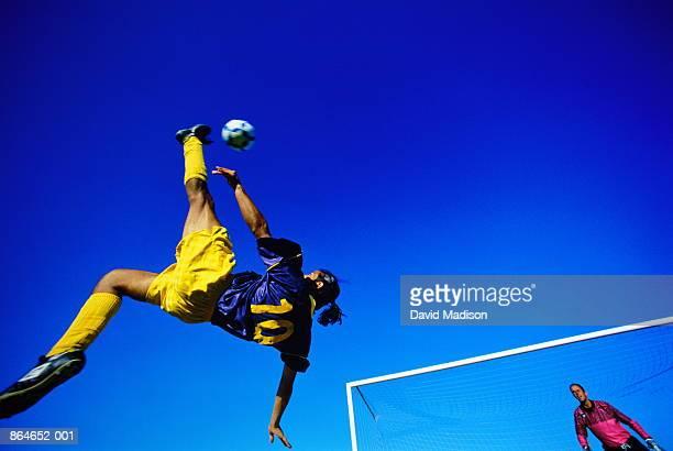 football, player doing overhead kick, goal in background, low angle - anfallsspelare fotboll bildbanksfoton och bilder