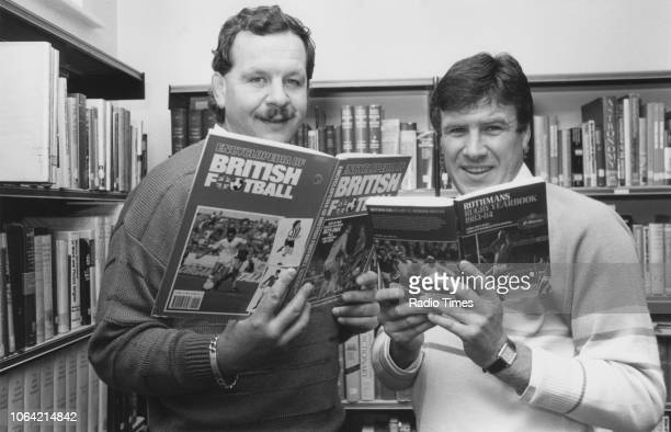 Football player Emlyn Hughes and rugby player Bill Beaumont pictured reading sports books in a library photographed for Radio Times in connection...