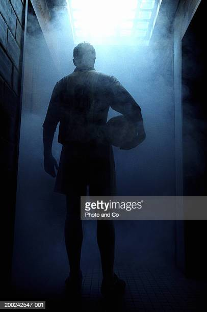 Football player entering steam room, rear view