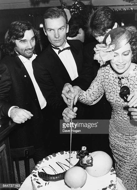 Football player George Best, singer Sting and actress Francesca Annis, cutting a celebration cake at an after party for the film 'Dune', at the club...