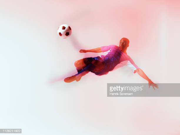 football player hanging in air, kicking - soccer player stock pictures, royalty-free photos & images