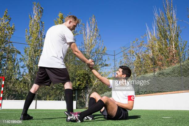 football player helping an injured player during a match - fair play sport foto e immagini stock