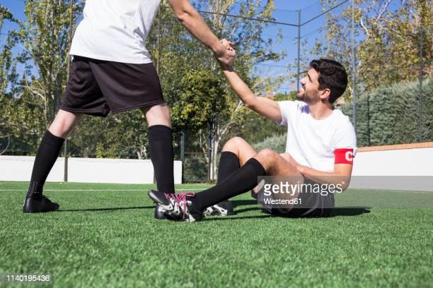 football player helping an injured player during a match - mannschaftskapitän stock-fotos und bilder