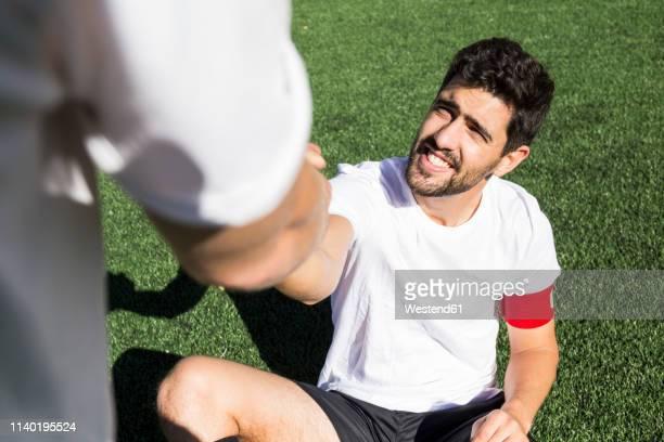 football player helping an injured player during a match - club football fotografías e imágenes de stock