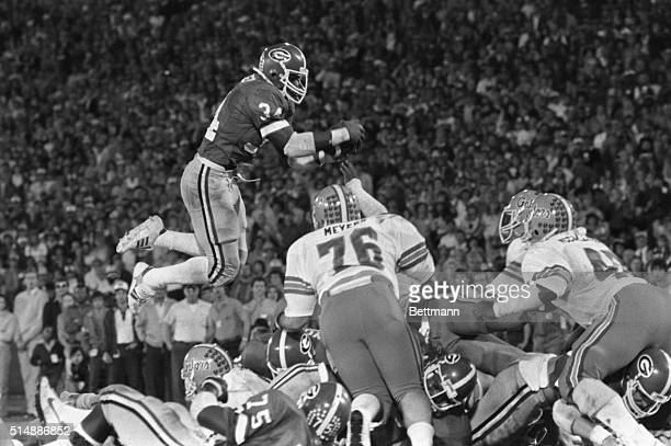 Football player Herschel Walker number 34 grabs the football from the air while playing for the University of Georgia football team