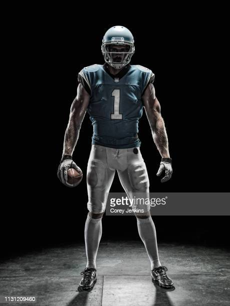football player holding ball - football player stock pictures, royalty-free photos & images