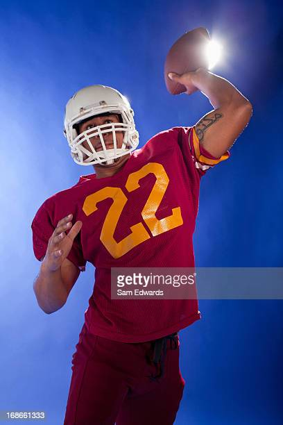 football player holding ball - quarterback stock photos and pictures