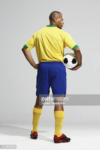 football player in a yellow and blue uniform standing against white background - traje de fútbol fotografías e imágenes de stock