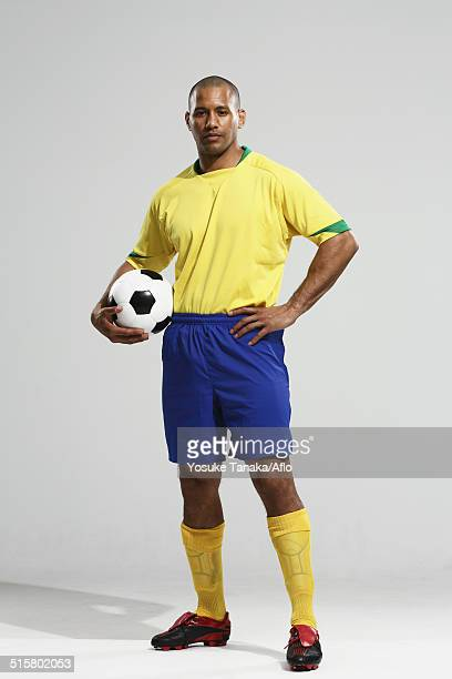 Football player in a yellow and blue uniform standing against white background