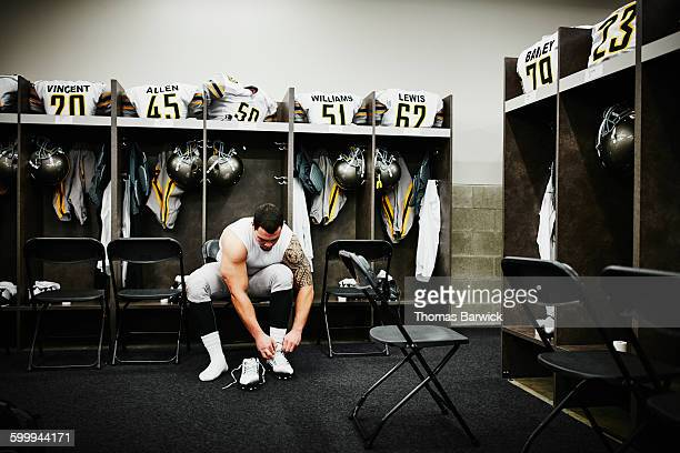 football player in locker room preparing for game - locker room stock pictures, royalty-free photos & images