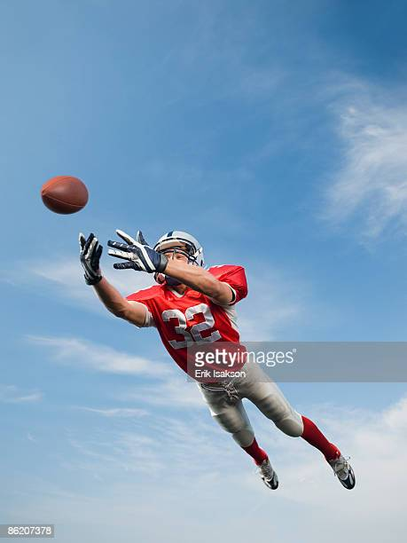 football player in mid-air reaching for football - wide receiver athlete stock pictures, royalty-free photos & images