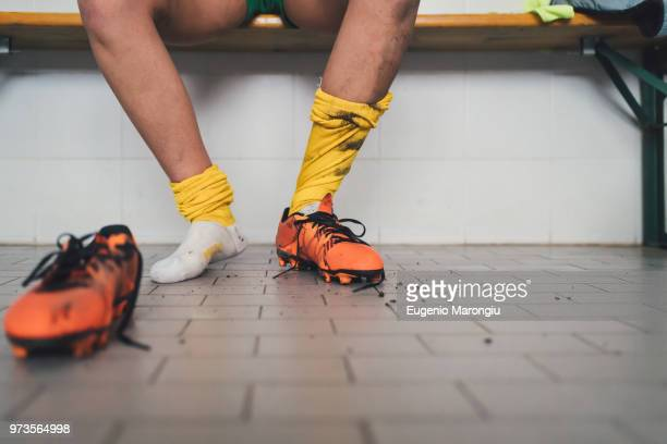 football player in one football boot in changing room - locker room stock pictures, royalty-free photos & images