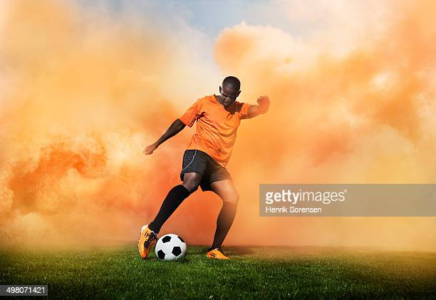 football player in orange smoke - drive ball sports stock pictures, royalty-free photos & images