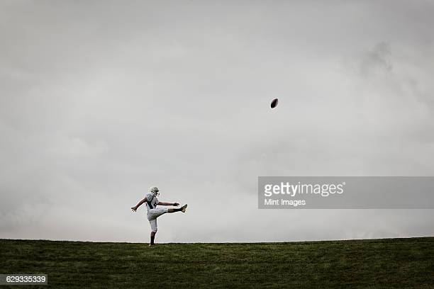 A football player in uniform, side view, practicing his kicking. Ball in mid air.