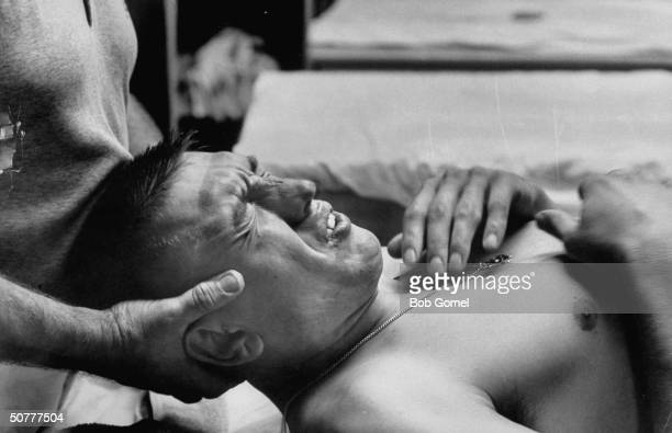 Football player Johnny Unitas of Baltimore Colts in trainers room for shoulder pain after a game