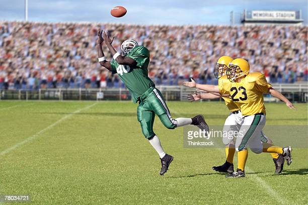 Football player jumping for ball during game