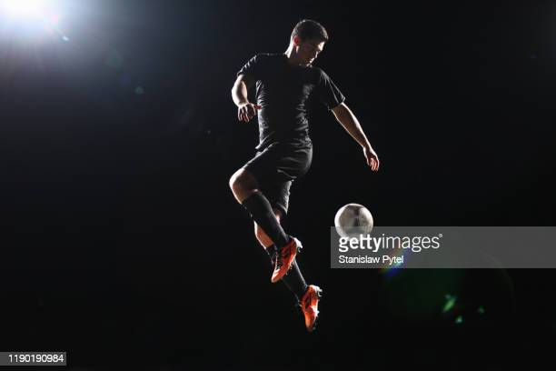 football player jumping with ball on dark background - athlete stock pictures, royalty-free photos & images
