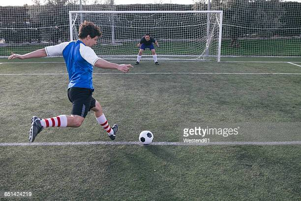 football player kicking a ball in front of a goal with a goalkeeper - scoring stock pictures, royalty-free photos & images