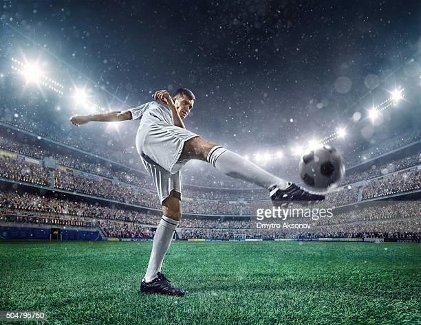 football player kicking a ball - soccer league stock pictures, royalty-free photos & images