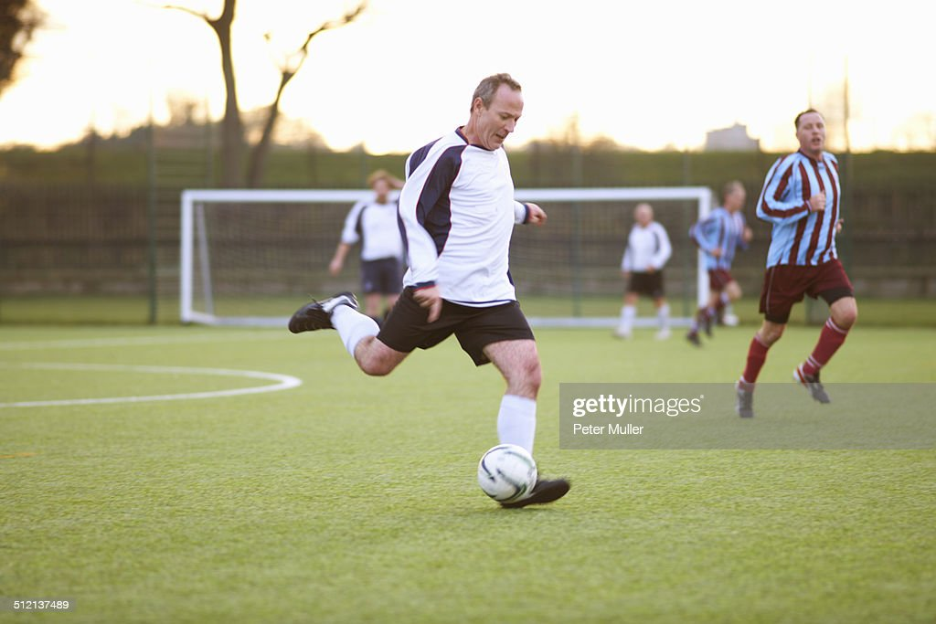 Football player kicking ball : Stock Photo