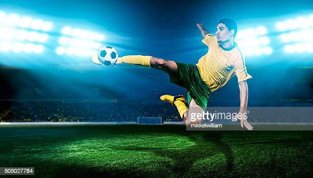 Football player kicks soccer ball in the air