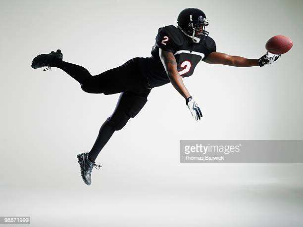 football player leaping in mid air to catch ball - safety american football player stock pictures, royalty-free photos & images
