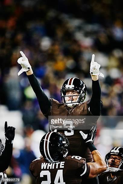 Football player lifting quarterback in air