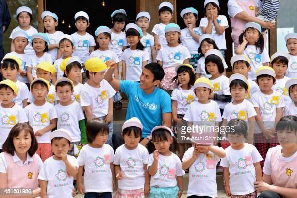 Football player Makoto Hasebe poses for photographs with pupils at Asahi Kindergarten during his visit to the tsunami devastated Minamisanriku on...
