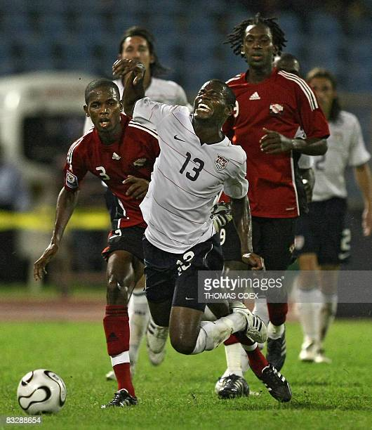 US football player midfielder Maurice Edu is tackled by Trinidad and Tobago' s defender Aklie Edwards and midfielder Keon Daniel during their FIFA...