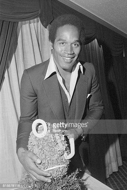 Football player O.J. Simpson poses with a football given to him at a luncheon by the Hertz Corporation to announce he has signed a new three-year...