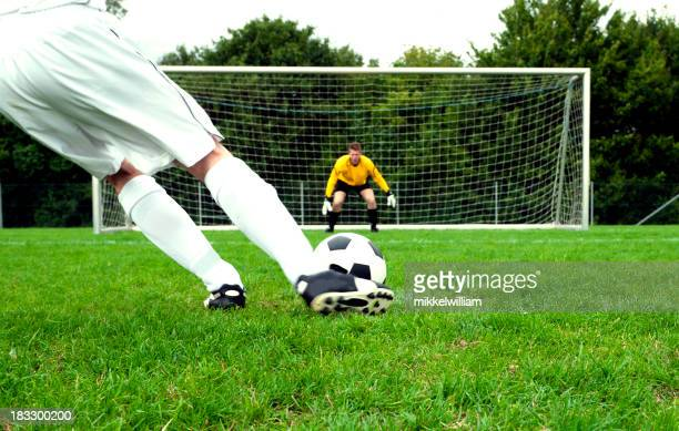 Football player performs a penalty kick on soccer pitch
