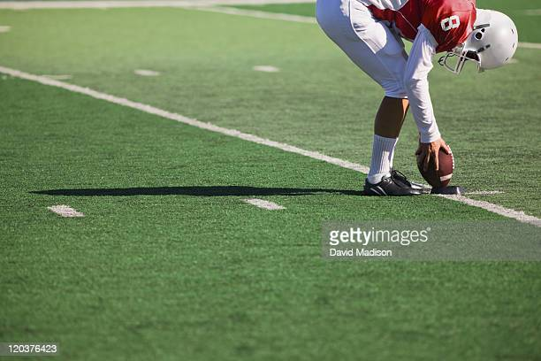 Football player places ball on kicking tee.