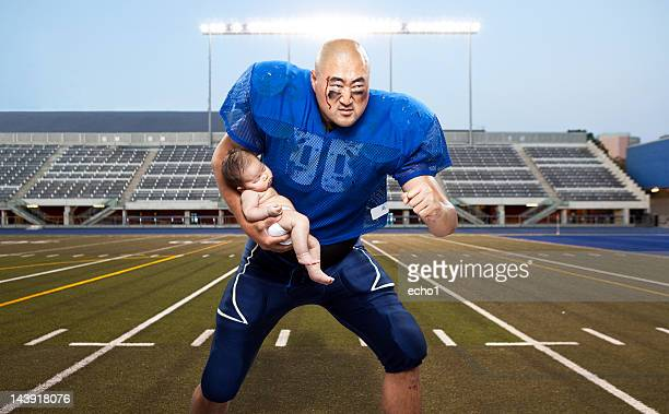 football player protecting baby - safety american football player stock pictures, royalty-free photos & images