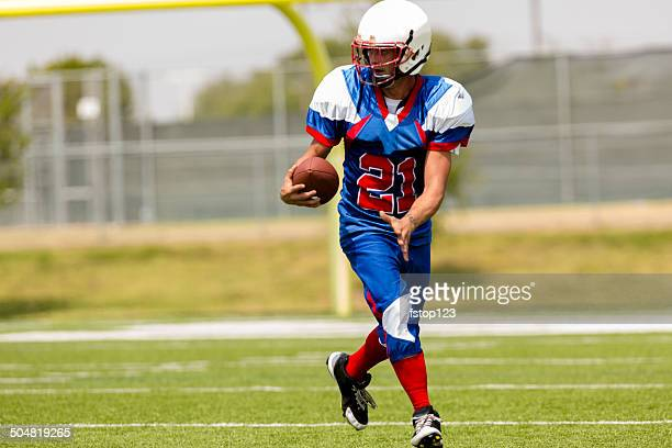 football player running with ball on playing field. goal post. - wide receiver athlete stock pictures, royalty-free photos & images