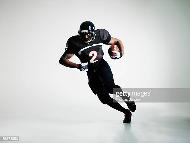 football player running with ball - football player stock pictures, royalty-free photos & images