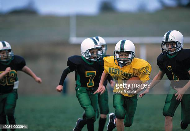 football player runs with ball - rush american football stock pictures, royalty-free photos & images