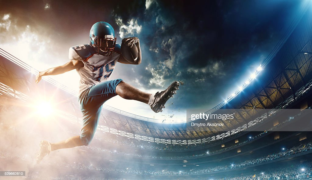 Football player runs with the ball : Stock Photo