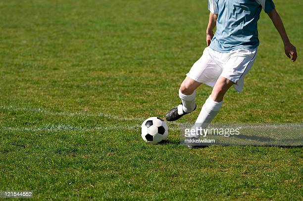 Fußball-Spieler Fußball ball schießt auf einem Feld
