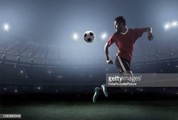football player showing skills with ball in stadium - torschuss stock-fotos und bilder
