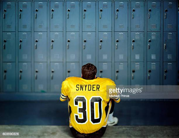 Football Player Sitting in Empty Locker Room