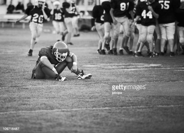 football player sitting on field - nederlaag stockfoto's en -beelden