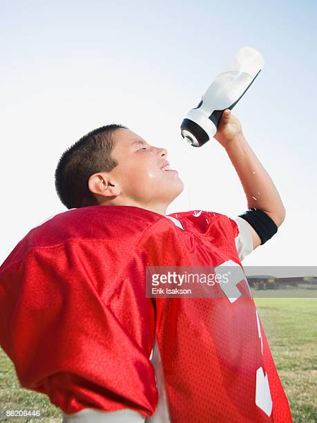 Football player spraying water on face