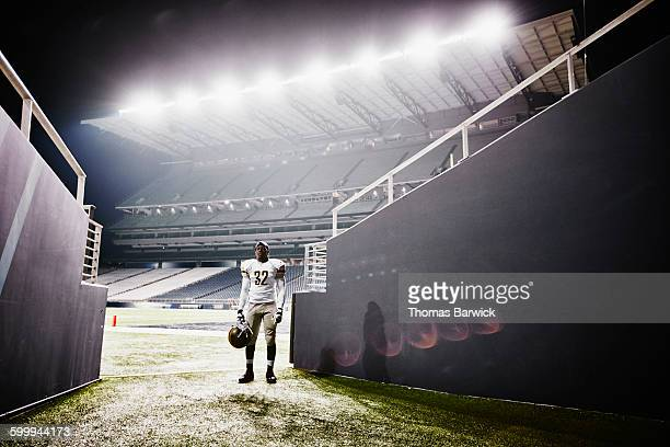 Football player standing at end of stadium tunnel