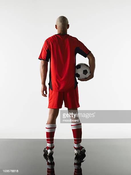 football player standing holding ball, back view - joueur de football photos et images de collection