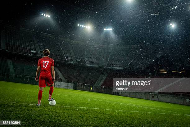 football player standing in stadium - voetbalveld stockfoto's en -beelden