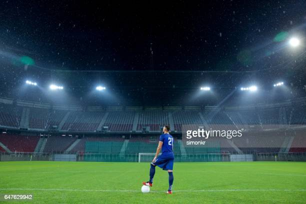 football player standing in stadium - stadio foto e immagini stock