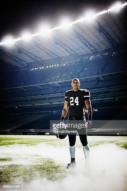 Football player standing on stadium field in fog